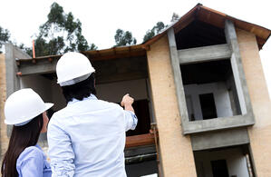 Architects at a construction site pointing at a house