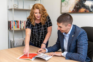 Man and woman look at brochure in office