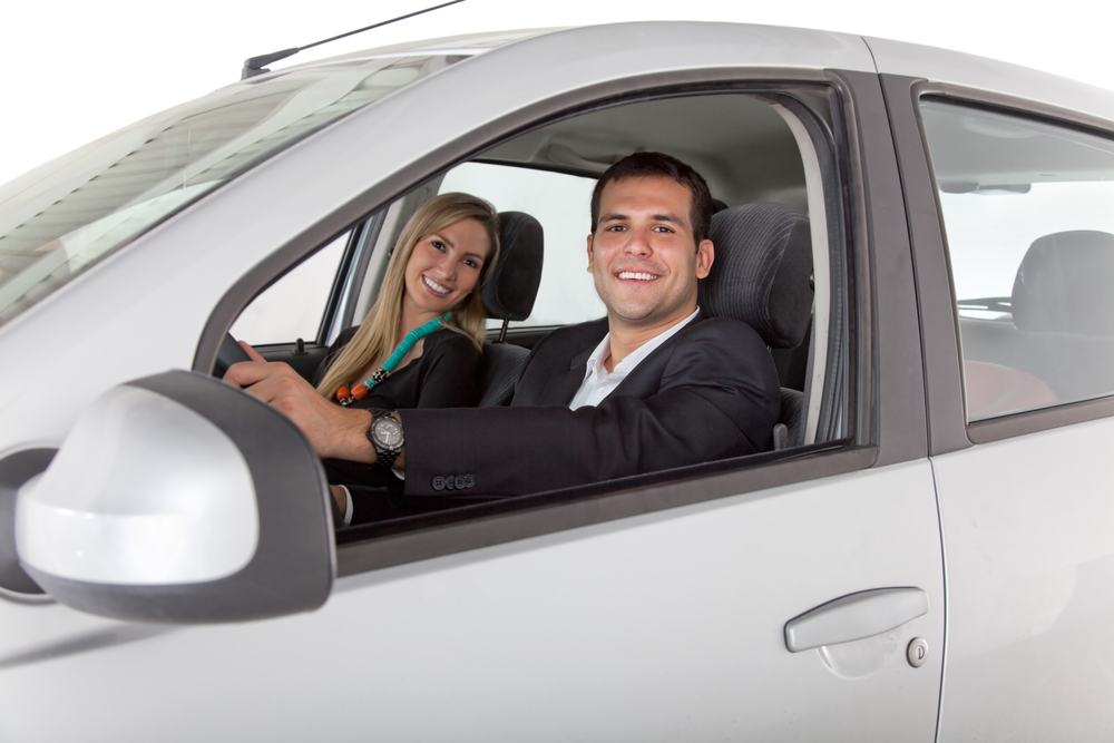 Couple with a car isolated over a white background
