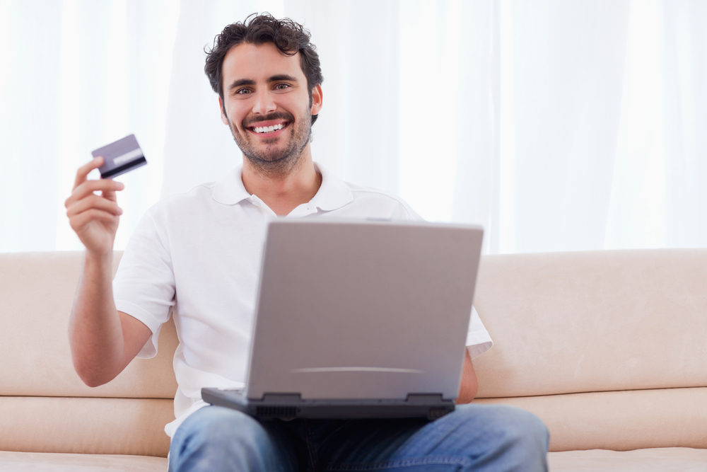 Happy man buying online in his living room